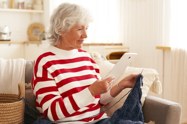 Ältere sechzigjährige frau mit grauem haar unter verwendung der digitalen tablette drinnen. ältere frau, die freizeit zu hause verbringt, auf dem sofa sitzt, serien online auf elektronischem gerät ansieht und strickt