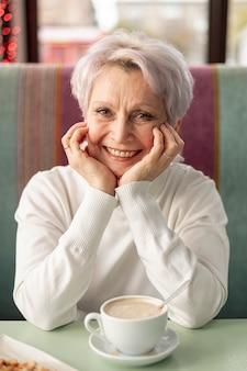 Ältere smileyfrau der vorderansicht am restaurant