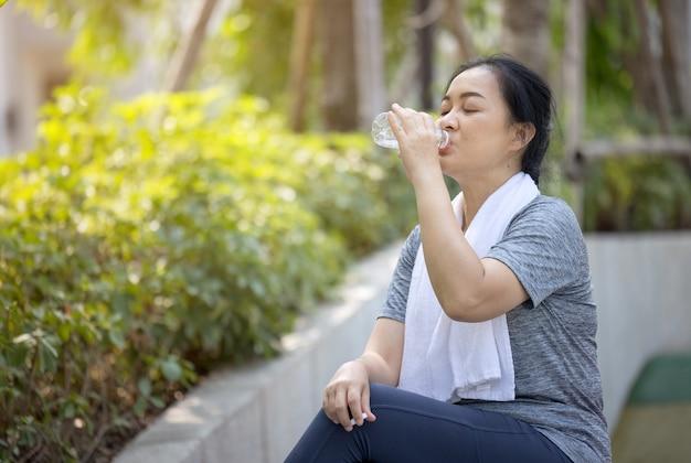 Ältere sportliche frau trinkt wasser aus einer flasche, nachdem sie im park gelaufen ist.