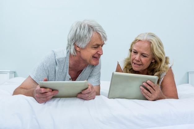 Ältere sprechende paare bei der anwendung von digitalen tabletten im schlafzimmer