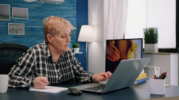 Ältere stilvolle frau, die notizen im notizbuch macht, während sie den laptop zu hause verwendet. alter freiberufler, der details zum buch schreibt, während er vom arbeitsplatz im wohnzimmer aus arbeitet und das finanzprojekt des unternehmens überprüft