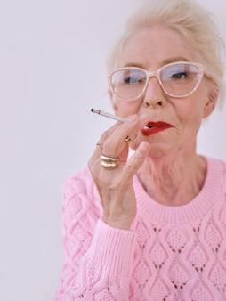 Ältere stilvolle frau, die zigarette raucht