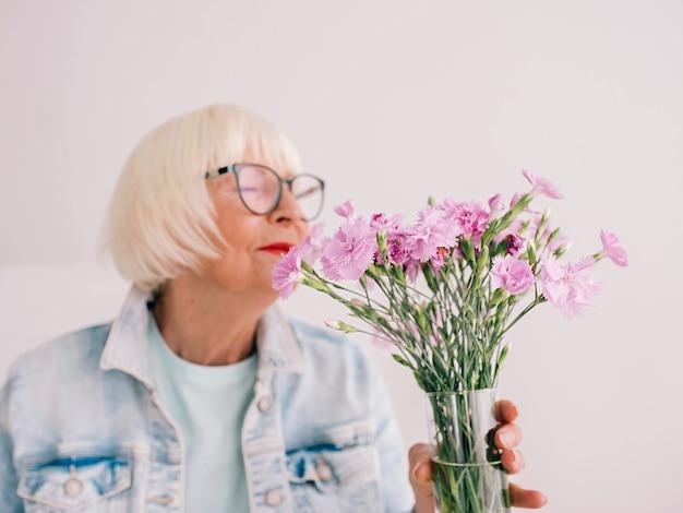 Ältere stilvolle frau in brille und jeansjacke riechen nelkenblumen in der vase