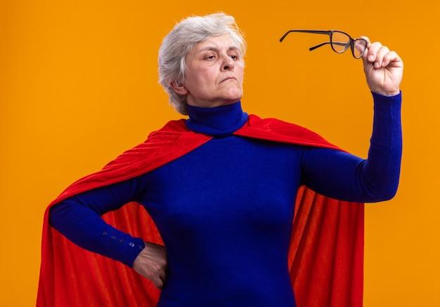 Ältere superheldin mit rotem umhang mit brille, die es mit ernstem gesicht betrachtet, das über orangefarbenem hintergrund steht