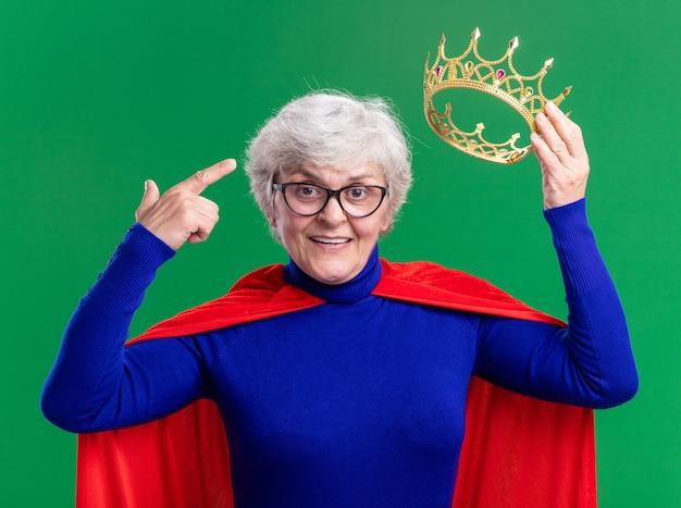 Ältere superheldin mit rotem umhang und brille, die eine krone hält und mit dem zeigefinger auf den kopf zeigt, lächelt selbstbewusst über grünem hintergrund