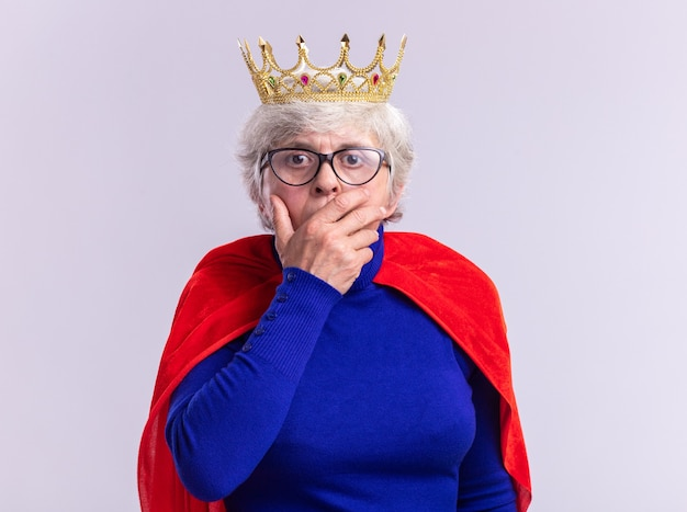 Ältere superheldin mit rotem umhang und brille mit krone auf dem kopf, die schockiert in die kamera schaut und den mund mit der hand auf weißem hintergrund bedeckt