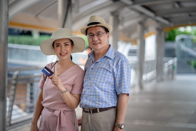 Ältere touristen der asiatischen paare, die das kreditkarteneinkaufen beim reisen halten