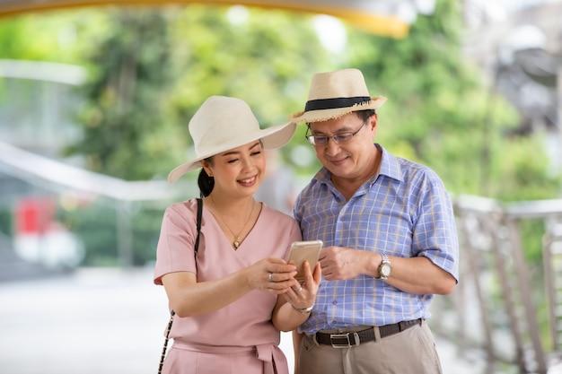 Ältere touristen, die am mobiltelefon schauen