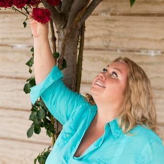 Ältere touristenfrau, die rosen während der reise genießt