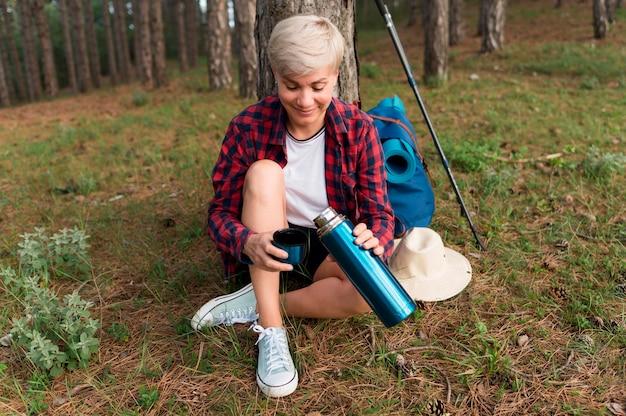 Ältere touristenfrau im freien mit thermoskanne