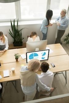 Ältere und junge angestellte, die im büro, obere vertikale ansicht arbeiten