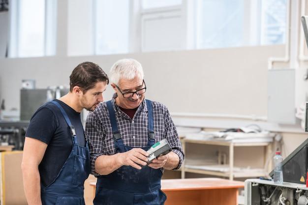 Ältere und junge druckarbeiter in overalls, die in der werkstatt stehen und ein scangerät zur untersuchung verwenden