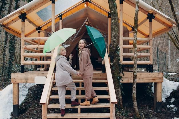 Ältere und junge erwachsene frauen mit regenschirm im glamping-campingzelt. modernes urlaubs-lifestyle-konzept.