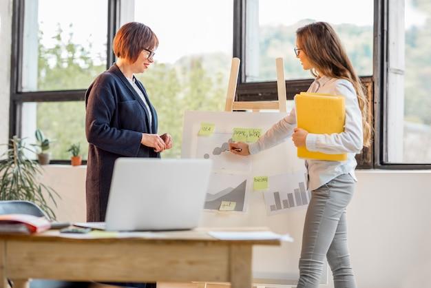 Ältere und junge geschäftsfrauen unterhalten sich in der nähe des vorstands mit finanzdiagrammen im büro am fenster