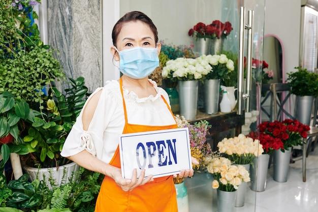 Ältere vietnamesische frau in der medizinischen maske, die offenes zeichen beim stehen im blumenladen zeigt