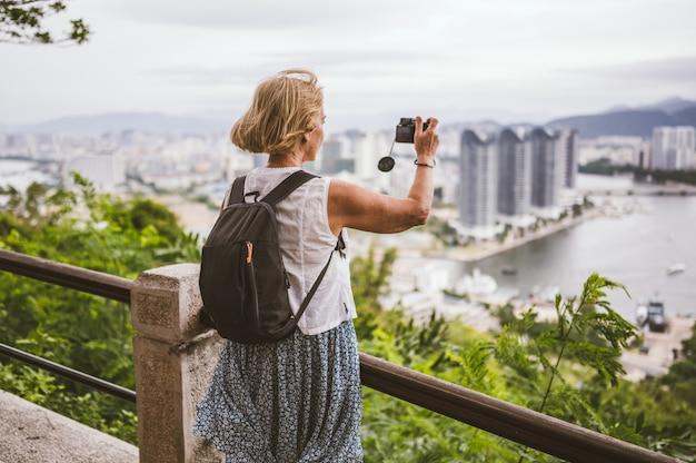 Ältere wandererfrau des reisenden, die fotos übersehen das stadtzentrum macht. reiseabenteuer in china, touristischer schöner bestimmungsort asien, sommerferien-urlaubsreise. konzept der freiheit und der glücklichen menschen