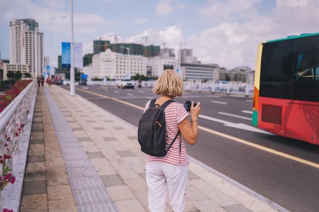 Ältere wandererfrau des reisenden, die in die asiatische stadt im stadtzentrum gelegen mit wolkenkratzern geht. reiseabenteuer-natur in china, touristischer schöner bestimmungsort asien, sommerferien-ferienreisereisekonzept