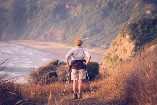 Ältere wandererin am strand von north piha