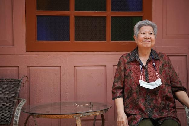 Ältere weibliche ältere frau der asiatischen alten älteren frau, die sich auf balkonterrasse entspannt. senioren freizeit lebensstil