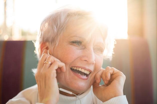 Ältere weibliche hörende musik des smiley
