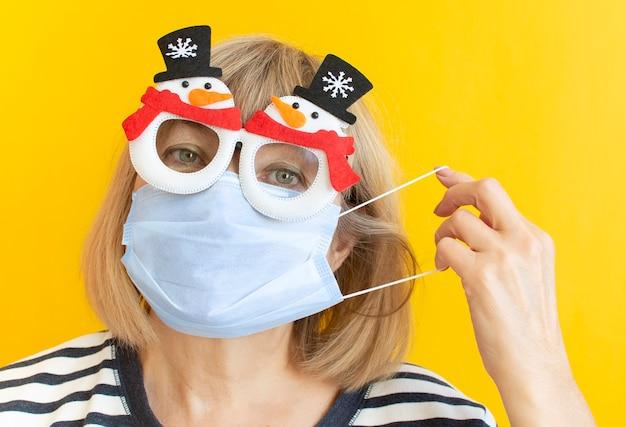 Ältere weihnachtsfrau, die schutzmaske und neujahrsbrille auf lokalem gelbem hintergrund trägt.