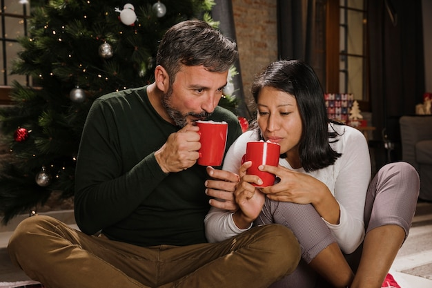 Ältere weihnachtspaare, die heiße schokolade trinken