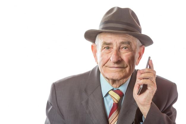 Älterer älterer alter mann mit einem retro-hut, der auf handy lokalisiert auf weißem hintergrund spricht.
