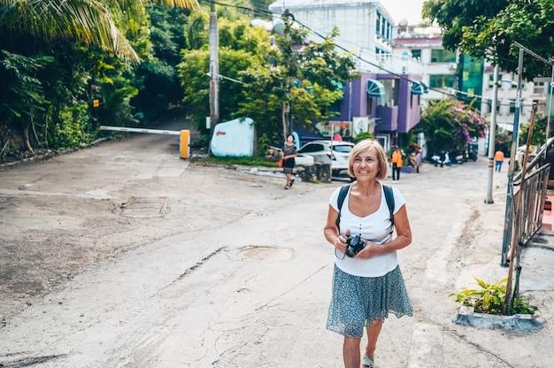 Älterer älterer asiatischer reisender reifer frauentourist des wanderers, der das machen von fotos in der lokalen straße sanya im freien genießt. entlang asien reisen, aktives lebensstilkonzept. entdecken sie hainan, china
