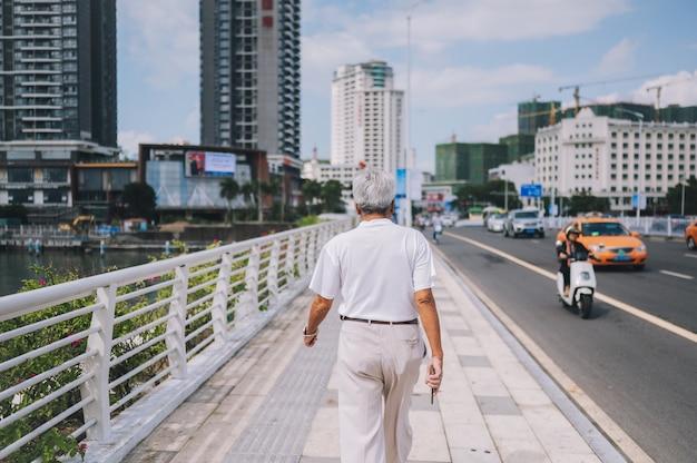 Älterer älterer mann des reisenden, der in die asiatische stadt im stadtzentrum gelegen mit wolkenkratzern geht. reiseabenteuer-natur in china, touristischer schöner bestimmungsort asien, sommerferien-ferienreisereisekonzept