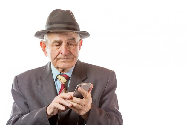Älterer älterer mann im retro-hut unter verwendung seines mobiltelefons lokalisiert auf weißem hintergrund.