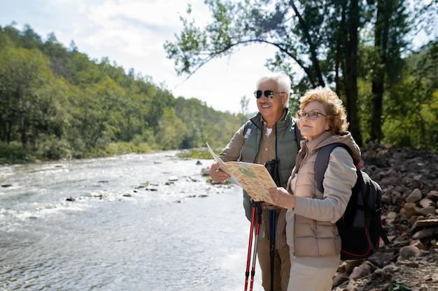 Älterer aktiver ehemann und ehefrau mit rucksäcken und karte, die gerade schauen, um ihre trekkingreise fortzusetzen