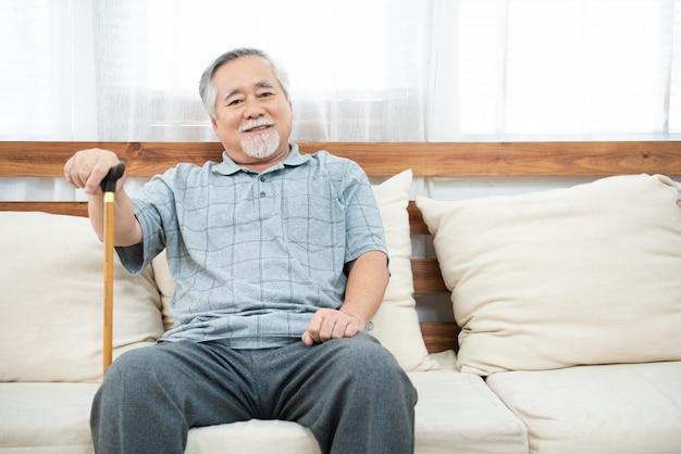Älterer alter älterer mann, der sitzt und seine hände auf hölzernem spazierstock ruht, der auf couch im wohnzimmer im haus nach ruhestand sitzt.