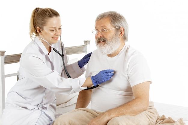 Älterer alter mann, der sich in einem krankenhausbett erholt, das auf weiß isoliert wird