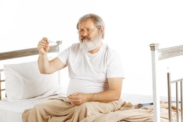 Älterer alter mann, der sich in einem krankenhausbett isoliert auf weißem hintergrund erholt. pflege bekommen. konzept des gesundheitswesens und der medizin. exemplar.
