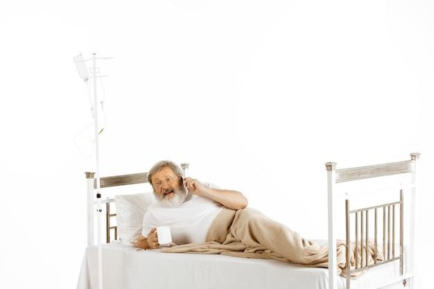Älterer alter mann erholt sich in einem krankenhausbett isoliert auf weiß