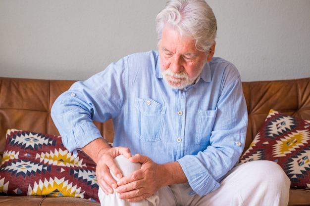 Älterer alter mann mit knieproblemen, der auf dem sofa sitzt und das knie zu hause hält. älterer mann, der unter starken knieschmerzen leidet, sitzt im wohnzimmer. älterer mann greift sich vor schmerzen am knie
