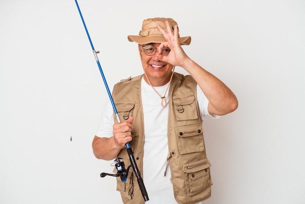 Älterer amerikanischer fischer, der stange lokalisiert auf weißem hintergrund hält, aufgeregt, ok geste auf auge zu halten.