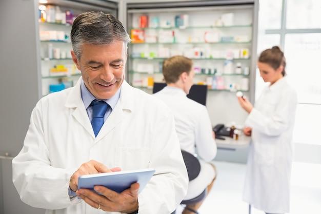 Älterer apotheker, der tabletten-pc verwendet