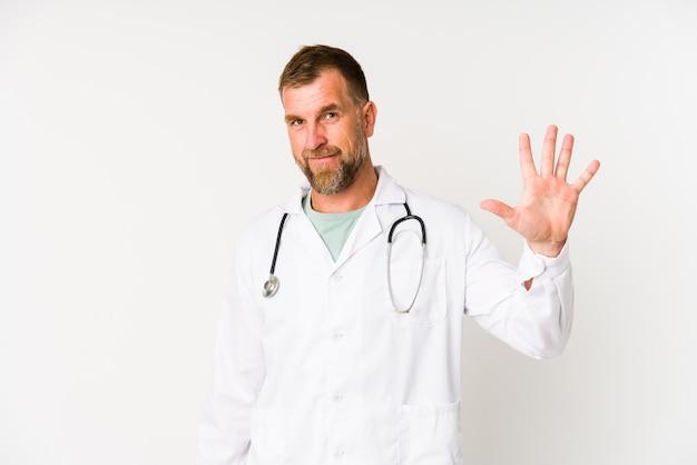 Älterer arztmann lokalisiert auf weißem hintergrund lächelnd fröhlich zeigt nummer fünf mit fingern.