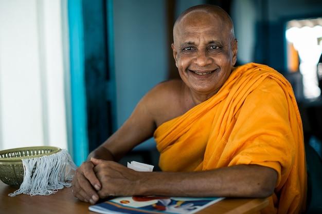 Älterer asiatischer buddhistischer mönch, der an der kamera im buddhistischen kloster in fluss lächelt