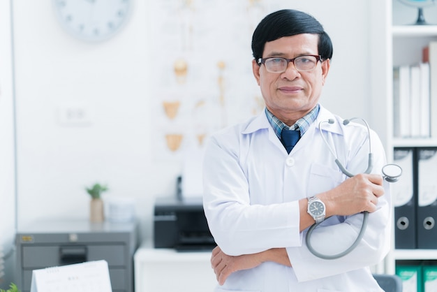 Älterer asiatischer doktor, der im prüfungsraum arbeitet