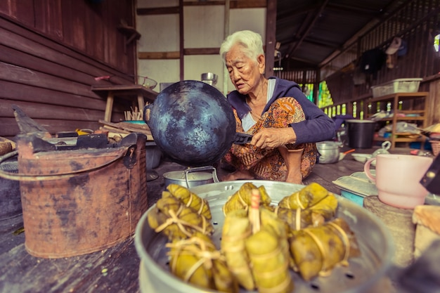 Älterer asiatischer frauenchefkoch in der küche, traditionell in thailand