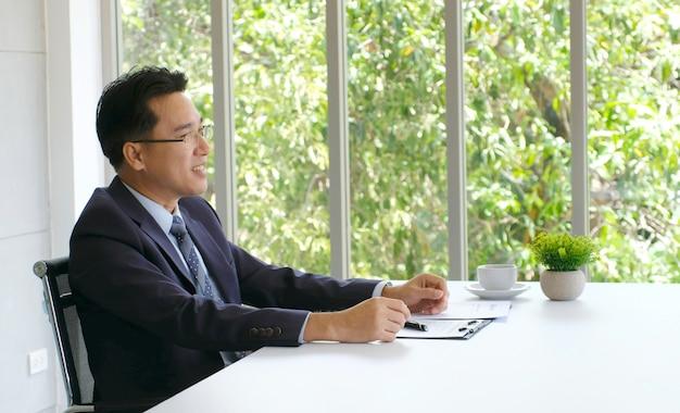 Älterer asiatischer geschäftsmann, der an dokument an seinem schreibtisch arbeitet