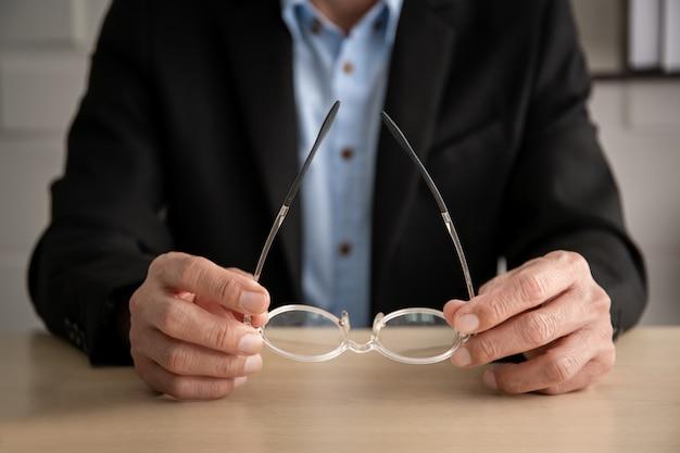 Älterer asiatischer manager im schwarzen anzug, der im büro sitzt und nah augengläser hochhält.