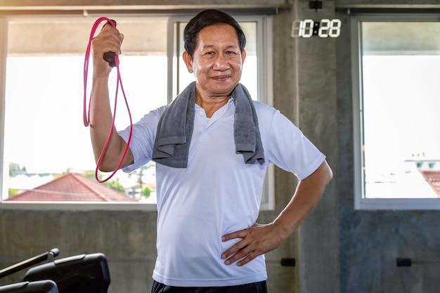 Älterer asiatischer mann, der im guten leben der sportkleidung lächelt.