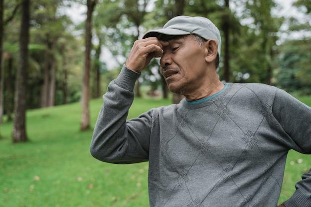 Älterer asiatischer mann, der kopfschmerzen hat