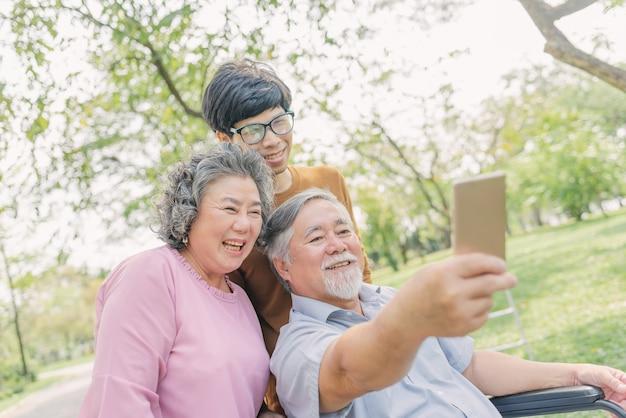 Älterer asiatischer mann, der smartphone für selfie mit seiner familie verwendet