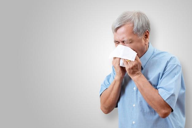 Älterer asiatischer mann hat grippe und niest vom krankheitsproblem der saison