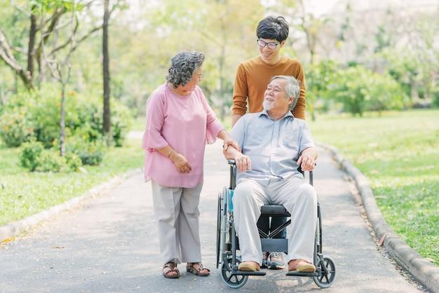 Älterer asiatischer mann im rollstuhl mit seiner frau und sohn