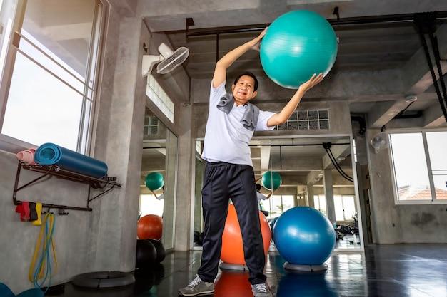 Älterer asiatischer mann in der sportkleidung bauchmuskeln mit ballturnhalle an der eignung ausbildend.